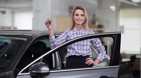 tuşları : Smiling woman shaking her keys behind new car Stok Video