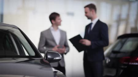 аренда : Close-up of the car in and people are discussing the conditions of purchase on background