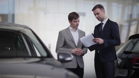 купить : Sales manager shows the customer a price list or car purchase contract Стоковые видеозаписи