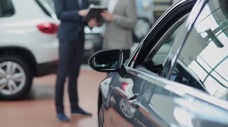 sprzedawca : Side-view mirror of a car and blurred customer and salesman who having a conversation on background Wideo