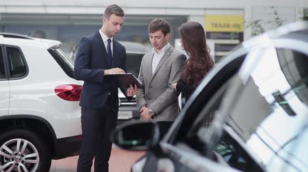 покупатель : Car salesman shows a young couple information about their new car