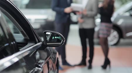 revendedor : Side-view mirror of a car and blurred people who familiarize with the price list in the background