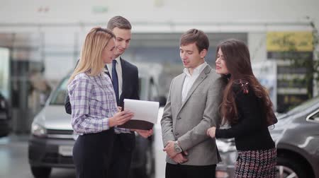 sprzedawca : Two sales manager showing price list of a car dealership to young couple that is going to make a purchase