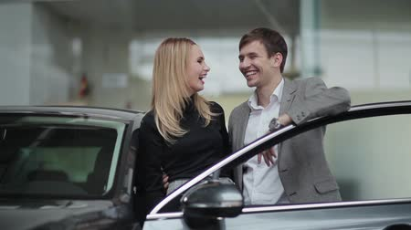 sprzedawca : Young couple near their new car in dealership