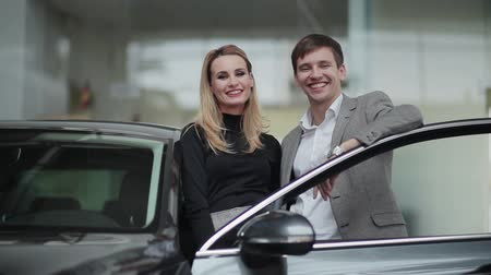 relação : Young couple near their new car in dealership