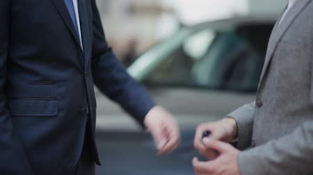 закрывать : Young guy buying a car from a dealer. Handshake between buyer and seller. Car seller hands over the keys to the buyer.
