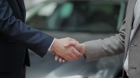 аренда : Double handshake after successful deal in car dealership Стоковые видеозаписи