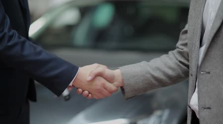 sprzedawca : Young guy buying a car from a dealer. Handshake between buyer and seller. Car seller hands over the keys to the buyer.