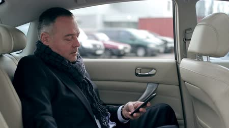 in : Businessman writing new contact to the phone while sitting on backseat of a car