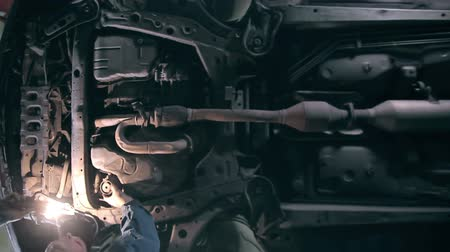 zkontrolovat : Mechanic examines the underside of a car at service station