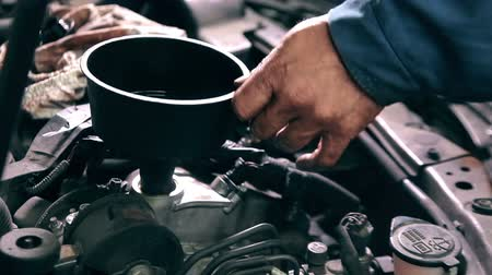 szerelő : Process of changing engine oil in car service station
