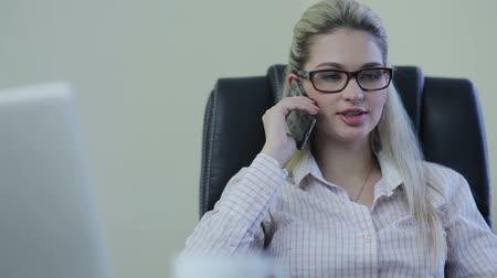 стулья : Young business woman sitting on a chair in the office talking on the phone Стоковые видеозаписи
