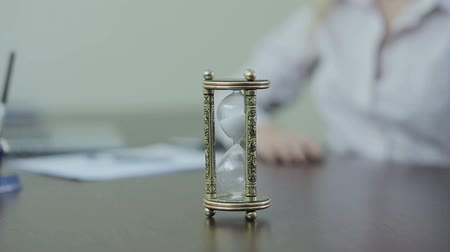 clock hands : Hourglass at office desk with blured businesswoman on background Stock Footage
