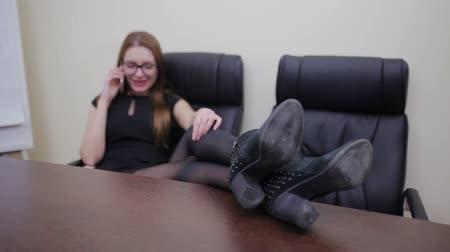 főnök : Young businesswoman sitting with legs on desk and talking on the phone in office Stock mozgókép