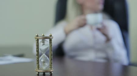 aguardando : Business woman turns hourglass and drinking coffee Stock Footage