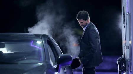 escape : Businessman filling a vehicle with fuel Stock Footage