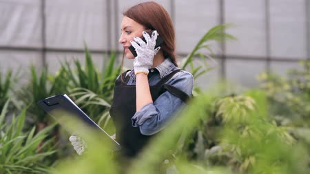 florista : Female gardener talking on the phone in greenhouse