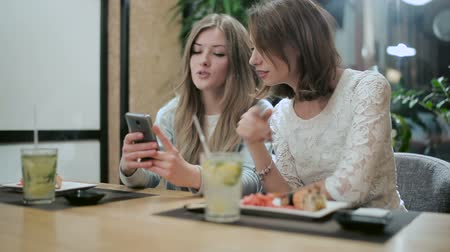 pronto a comer : Two girls are considering something on smartphone Stock Footage