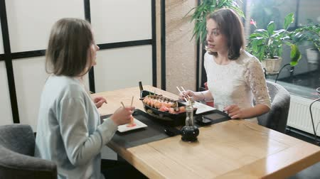 comida japonesa : Girlfriend eating sushi and rolls and gossiping