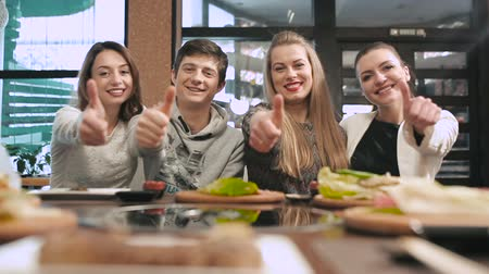 négy ember : Group of friends showing thumbs up in restaurant Stock mozgókép