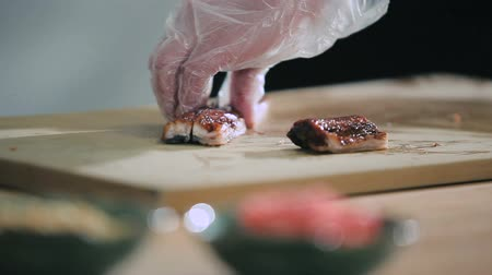 comida japonesa : Sushi master cuts fish on a cutting board