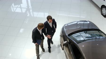 покупатель : Salesman helping customer to choose a car Стоковые видеозаписи