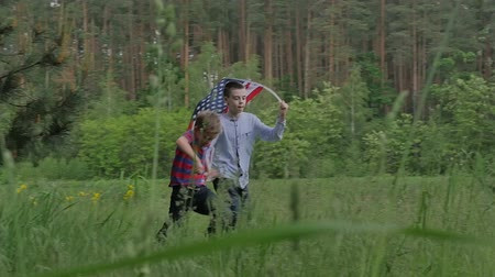 июль : Two boys running in the forest with US flag