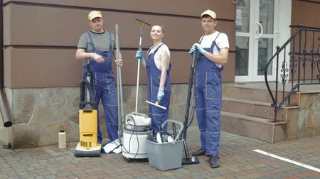 cleaning equipment : Three cleaner stand near the steps to the door.