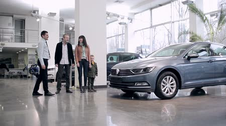 купить : Seller meets family in a car showroom Стоковые видеозаписи