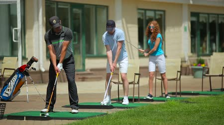 manges : Young people play golf near the clubhouse Stock Footage