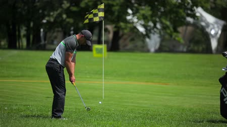 manges : Man tries to get the ball in hole at golf field