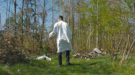 manges : The guy goes through the woods among garbage heaps