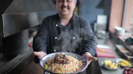 frango : The chef shows on camera plate of pilaf with lamb.