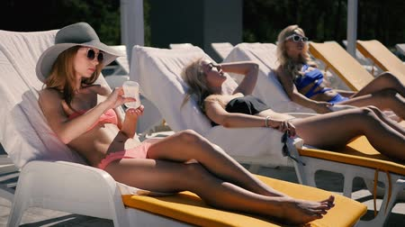 протирать : Three girls are relaxing near the swimming pool Стоковые видеозаписи