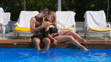 hot beverage : Young couple are relaxation near the swimming pool Stock Footage