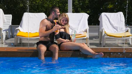 banhos de sol : Young couple are sunbathing near the swimming pool Vídeos