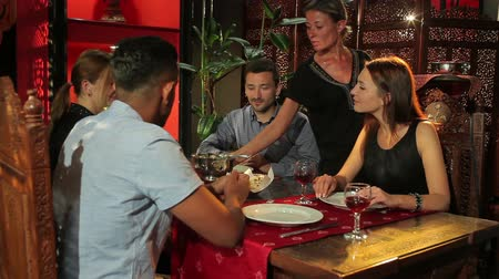 porce : The waiter brings meal for clients in restaurant