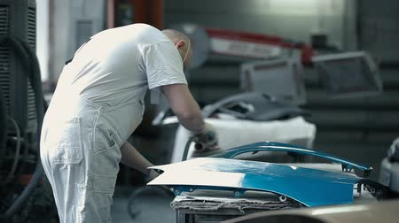 repaint : Master polishes the details of the car bumper.