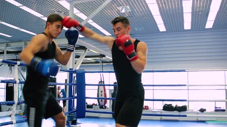 male : Athletes are boxing in the ring.