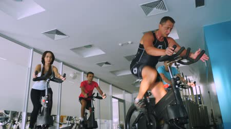 equipamentos esportivos : Old trainer training young sportmen the cycling on the exercise bike in the gym