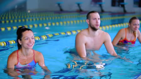 esportivo : Two young women and man doing water aerobics in the swimming pool