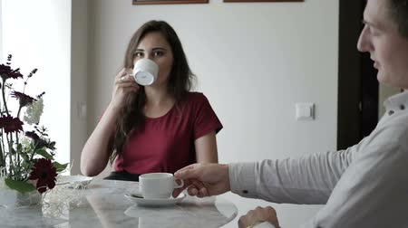 compatibility : A woman picks up a cup with a drink on the table.