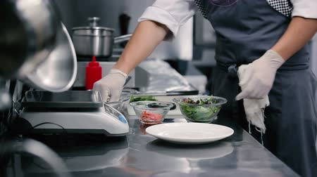 cooks : Cook stirs the leaves of lettuce. Stock Footage