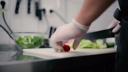 cooks : Cook slices cherry tomatoes. Stock Footage