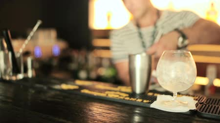 straining : The bartender pours water from a shaker.