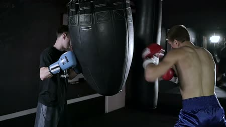 zsák : Coach holds the punching bag for his sportsman.
