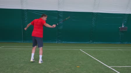 tennis stadium : Man playing tennis with young guy on grass court Stock Footage