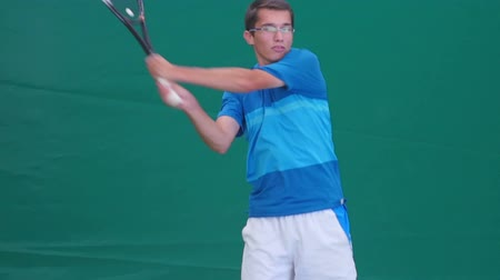 tennis stadium : The athlete holds the racket with both hands and playing tennis Stock Footage
