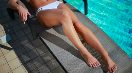 nogi : Woman with slim legs sunbathing near the swimming pool