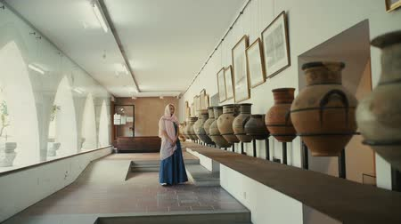 terrakotta : Beautiful woman visits a museum with antique pots and pictures